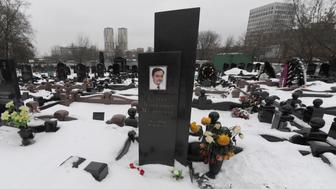 A picture taken on December 7, 2012, shows  snow clad grave of Russian lawyer Sergei Magnitsky with his portrait on the tomb (C) at the Preobrazhenskoye cemetery in Moscow. The US Congress drew today a furious response from the Kremlin by passing legislation that targeted human rights abusers in the prison death of Magnitsky. Moscow immediately called the action 'a theater of the absurd' and vowed to retaliate, turning what would have been a boost in trade relations between the two powers into another source of friction.  AFP PHOTO / ANDREY SMIRNOV        (Photo credit should read ANDREY SMIRNOV/AFP/Getty Images)