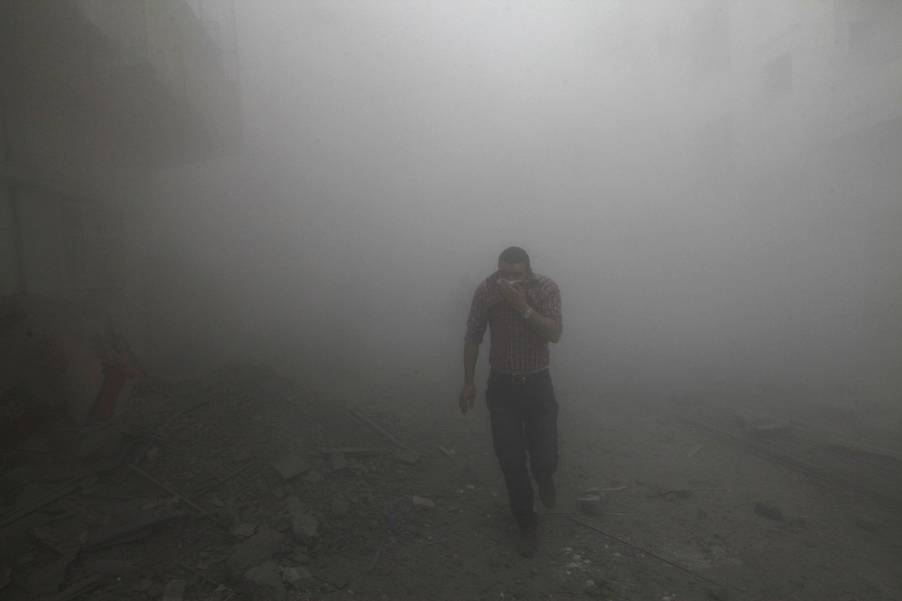 A man runs amongst rubble as smoke rises from buildings damaged by what activists said were missiles fired by a Syrian Air Force fighter jet loyal to President Bashar al-Assad in Raqqa province, eastern Syria, March 12, 2013. REUTERS/Hamid Khatib (SYRIA - Tags: CONFLICT TPX IMAGES OF THE DAY)