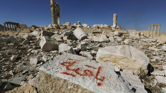 "Graffiti sprayed by Islamic State militants which reads ""We remain"" is seen on a stone at the Temple of Bel in the historic city of Palmyra, in Homs Governorate, Syria April 1, 2016. REUTERS/Omar Sanadiki  SEARCH ""PALMYRA SANADIKI"" FOR THIS STORY. SEARCH ""THE WIDER IMAGE"" FOR ALL STORIES"