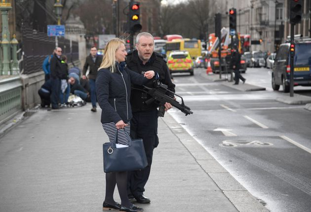 An armed police officer assists a member of the public on Westminster
