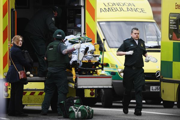 A member of the public is moved into an ambulance by emergency services near Westminster Bridge.