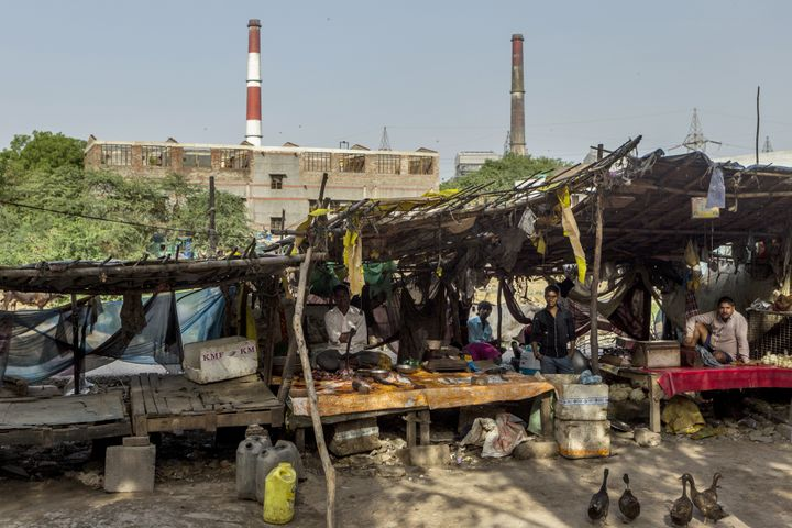 Vendors sit at stalls as smokestacks stand in the background at a coal-fired power plant in Badarpur, Delhi, India, on M