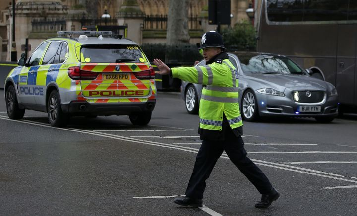 Theresa May's armoured Jaguar (right) drives past police officers in the seconds after it became clear Westminster was under attack