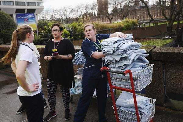 Nurses from St. Thomas' Hospital load blankets outside the hospital.