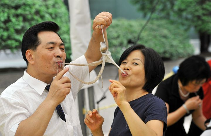 A South Korean man and a woman eat a live octopus during an event to promote a local food festival in Seoul on Sept. 12, 2013.