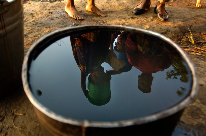 Young women in Malawi, Africa, are reflected in a bucket of water as they prepare to make the long hike back to their homes a