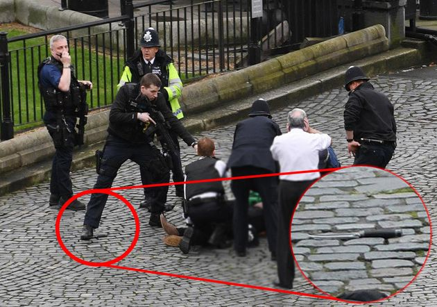A police officer stands on top of a knife while aiming his gun at the suspected attacker outside
