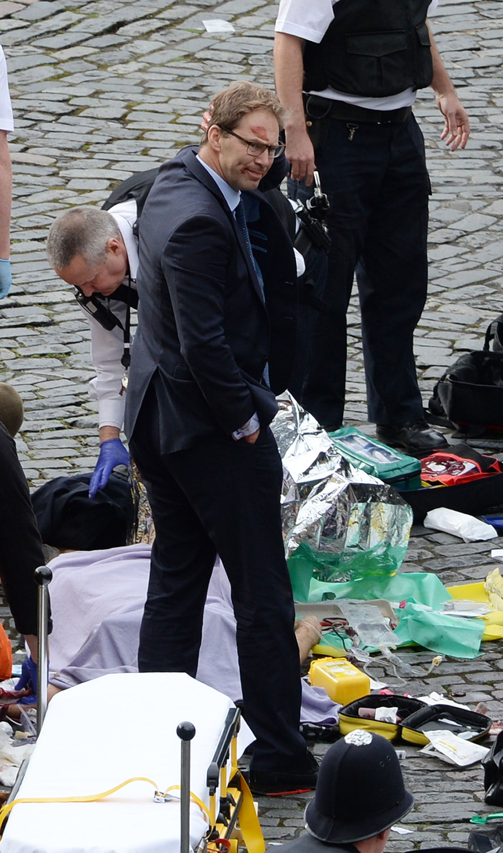 NOTE ALTERNATE CROP Conservative MP Tobias Ellwood stands amongst the emergency services at the scene outside the Palace of W