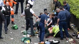 RETRANSMISSION ADDING TOBIAS ELLWOOD TO THE CAPTION Conservative MP Tobias Ellwood (centre, in group at bottom right) helps emergency services attend to a police officer at the scene outside the Palace of Westminster, London, after a policeman was stabbed and his apparent attacker shot by officers in a major security incident at the Houses of Parliament. (Photo by Stefan Rousseau/PA Images via Getty Images)