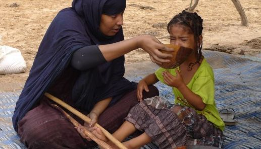 A Mauritanian woman force-feeding a young girl.