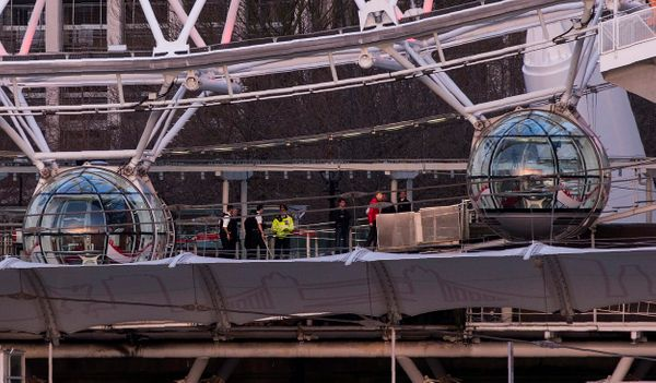 British police officers stand between the pods of the London Eye, as passengers are evacuated.