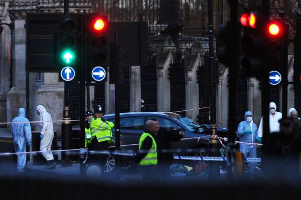 British police forensics officers work near a gray vehicle that crashed into the railings of the Houses of Parliament.