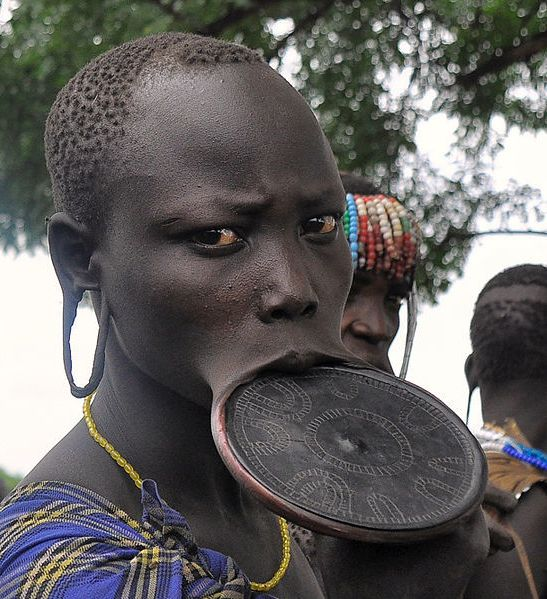 A Mursi woman displays her lip plate.