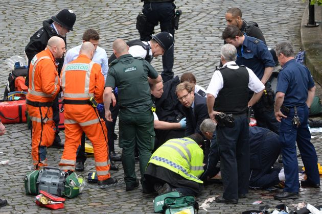 Conservative MP Tobias Ellwood (centre) helps emergency services attend to a police officer outside the...