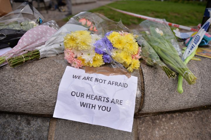 Floral tributes are seen near a police cordon in Westminster in central London a day after a deadly terror attack.