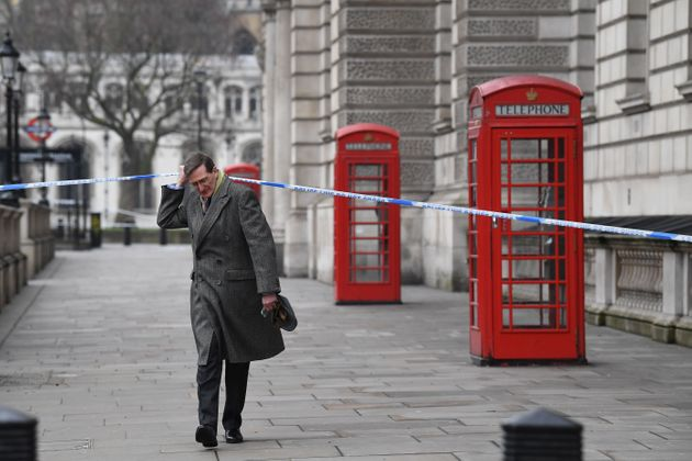 Dominic Grieve passes through the police cordon as he walks along