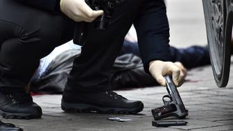 EDITORS NOTE: Graphic content / An Ukrainian police expert seizes a gun at the scene where former Russian MP Denis Voronenkov was shot dead on March 23, 2017 in the center of Kiev. Ukrainian President blamed Russia for the murder of Voronenkov, who moved to Ukraine last year and was wanted by Russia for fraud, saying it was an 'act of state terrorism.'  / AFP PHOTO / Sergei SUPINSKY        (Photo credit should read SERGEI SUPINSKY/AFP/Getty Images)