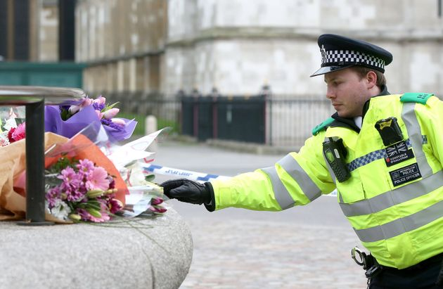 A police officer rearranges floral tributes to those killed in the
