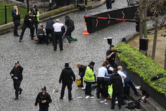 An officer points a gun at Masood, top left, following the stabbing of PC Palmer, bottom