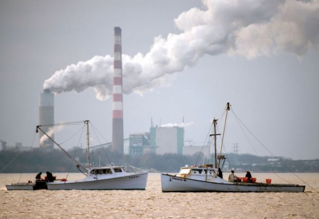 Two fishing boats anchored in front of a power plant on the Chesapeake Bay. Part of the federal cleanup effort in the region