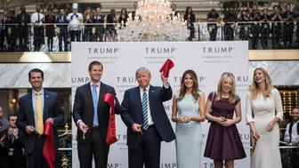 WASHINGTON, DC - OCTOBER 26: Republican presidential candidate Donald Trump, accompanied by, from left, Donald Trump Jr., Eric Trump, Trump, Tiffany Trump, Melania Trump,  and Ivanka Trump, holds up a ribbon during the grand opening ceremony of the Trump International Hotel- Old Post Office in Washington, DC on Wednesday October 26, 2016.  (Photo by Jabin Botsford/The Washington Post via Getty Images)