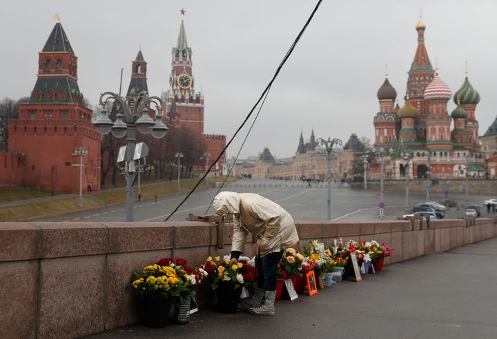 A woman adjusts flowers at the site of the 2015 assassination of Kremlin critic Boris Nemtsov in central Moscow on Monday.