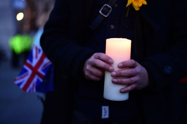 A member of the public holds a candle during the candlelight vigil in Trafalgar Square, London to remember...