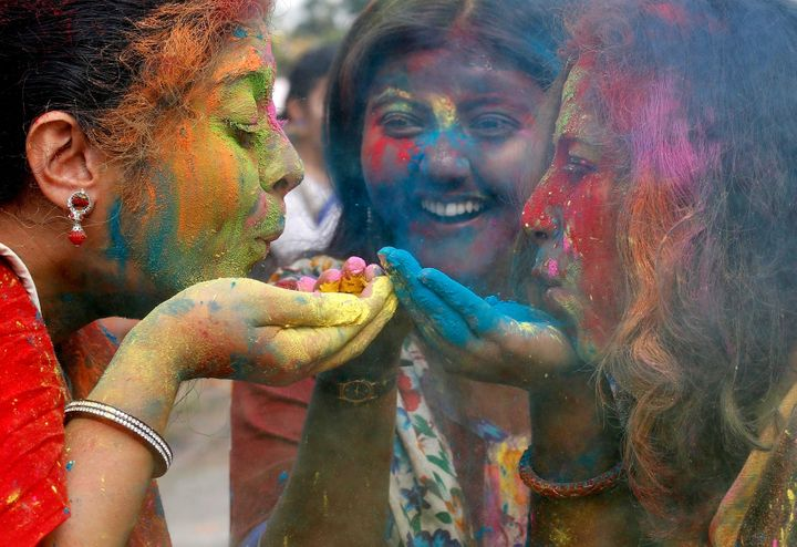 Students of Rabindra Bharati University blow colour powder during Holi, the Festival of Colours, celebrations inside the univ