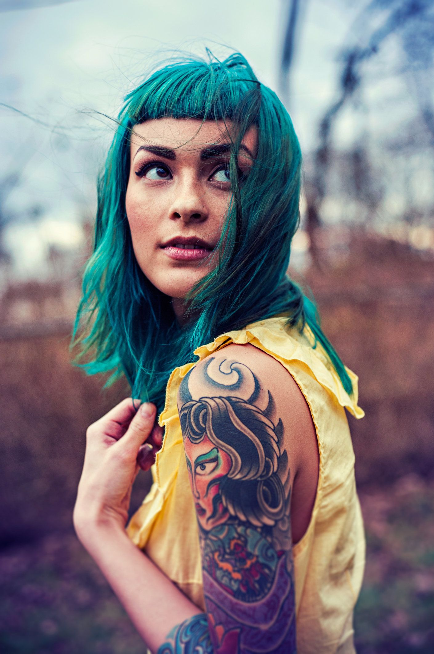 Portrait of young woman with blue hair and tattoos looking up over her shoulder.