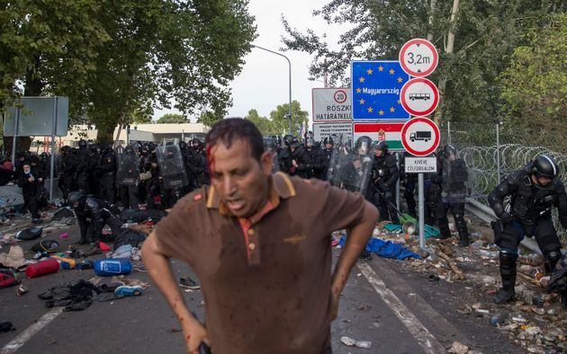 A migrant stands after clashing with Hungarian riot police at the border crossing with Serbia in Roszke,...