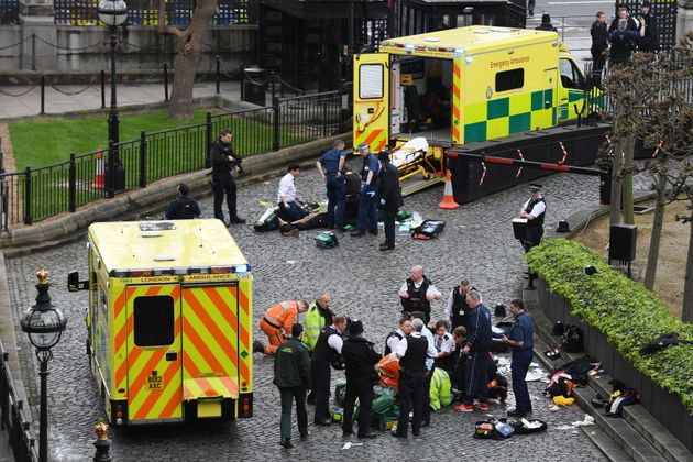 Emergency services attend a man (top) and a police officer (bottom) outside the Palace of Westminster...
