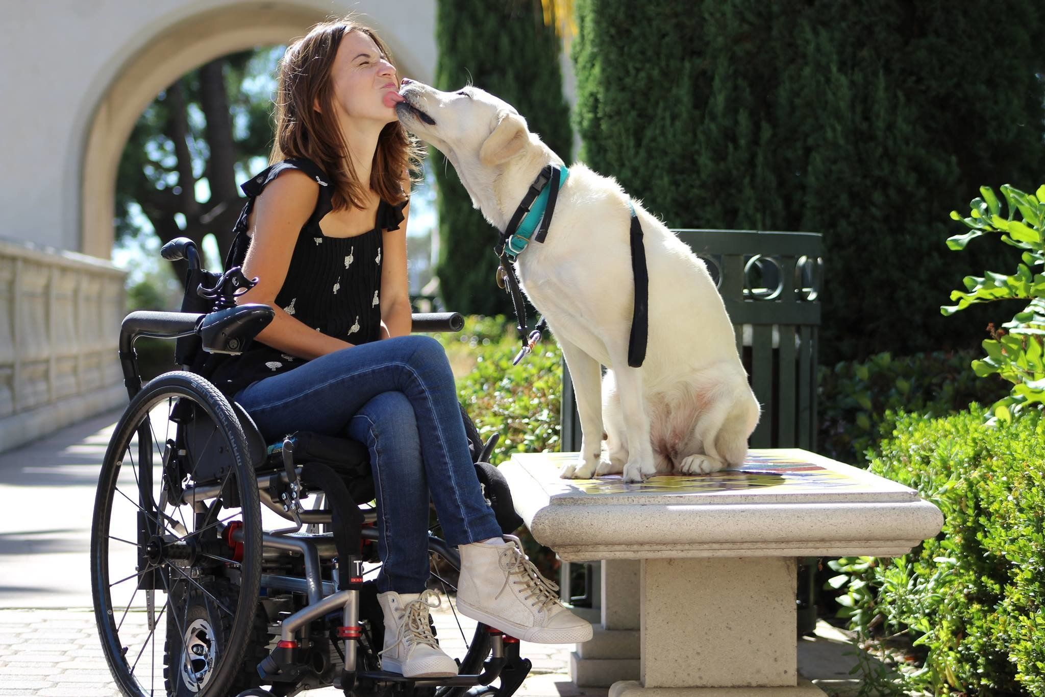 Daniela Schirmer receives a kiss from Zandra, her Labrador service dog.