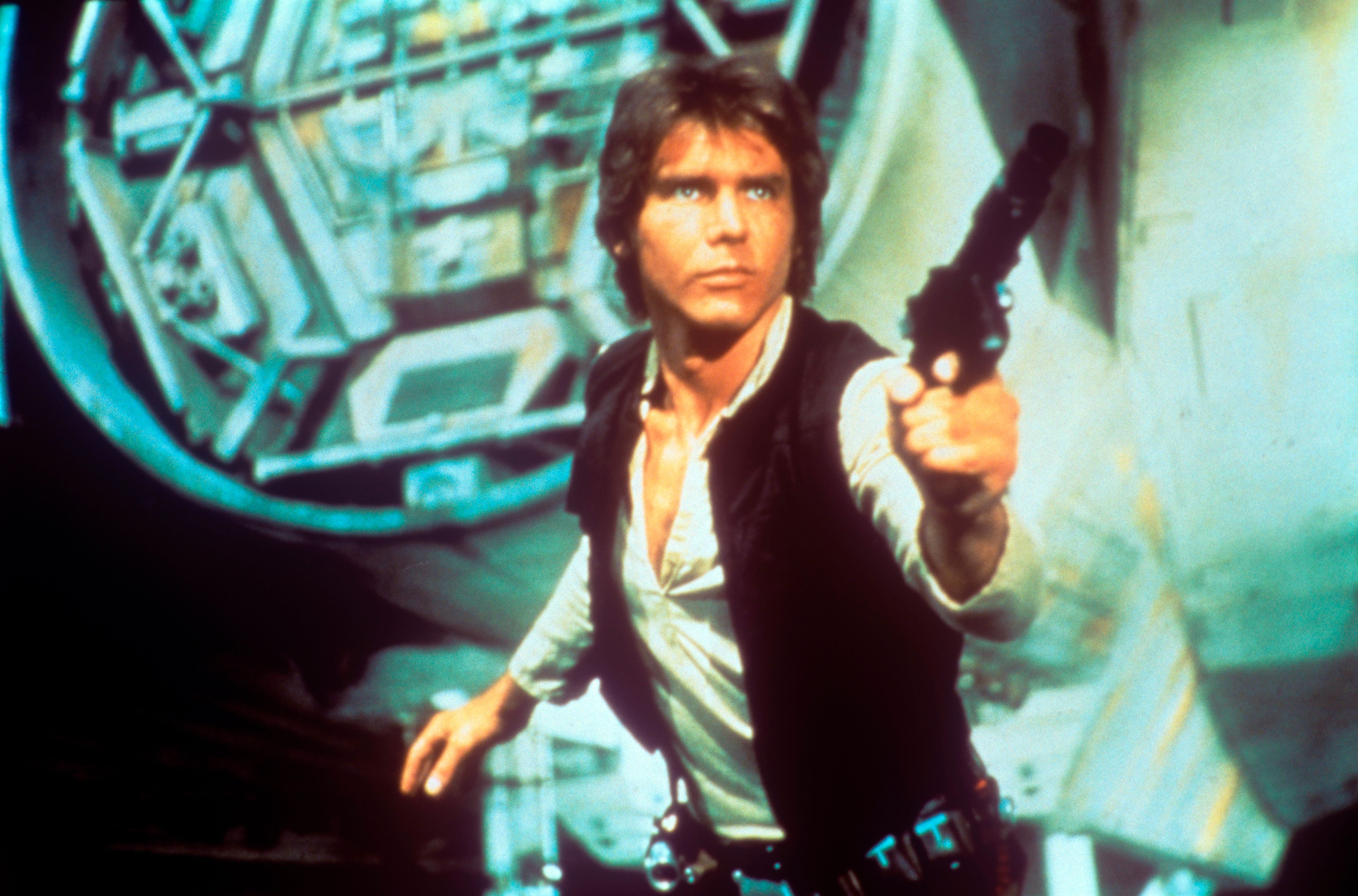 In a scene from George Lucas' epic space opera Star Wars, the American actor Harrison Ford as rebel smuggler Han Solo draws a gun against enemies; behind him can be seen a fantastic space shuttle. USA, 1977. . (Photo by Mondadori Portfolio via Getty Images)