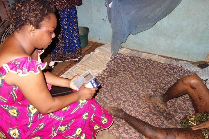 <p>Isabelle using the CommCare application during her home visit with Aka.</p>