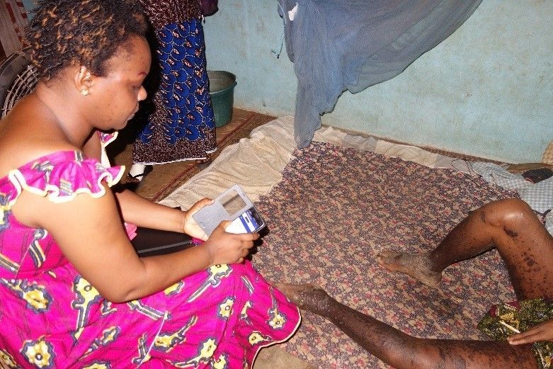 Isabelle using the CommCare application during her home visit with Aka.