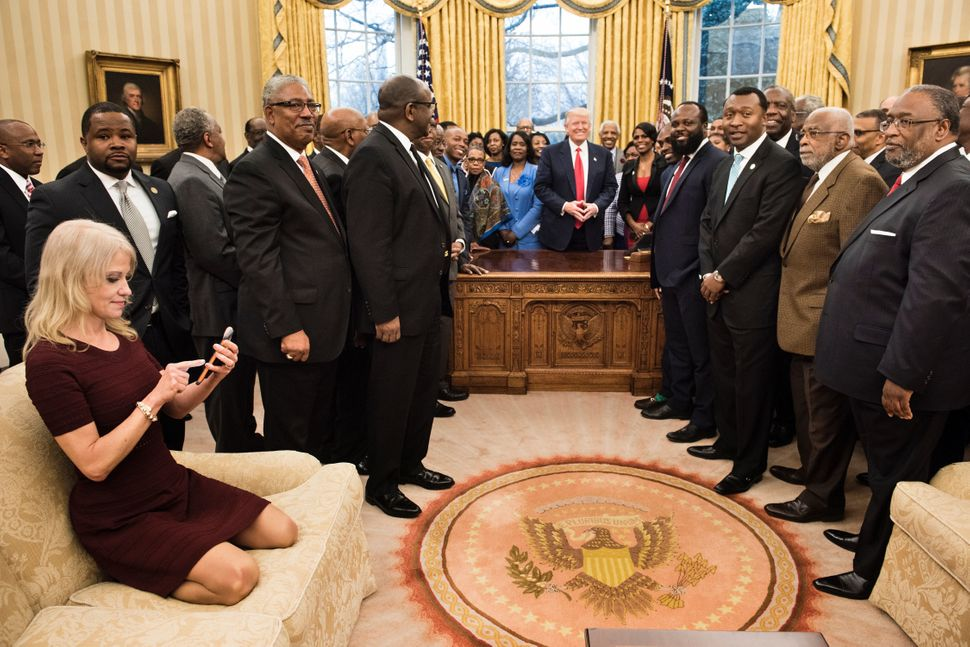Trump counselor Kellyanne Conway, left, checks her phone after taking a photo as Trump and leaders of historically black univ