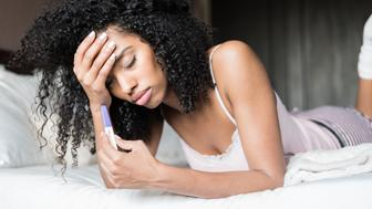 woman on bed sad and worried with a pregnancy test