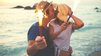 Two people holding sparklers and kissing on the mouth ,celebrating anniversary on the beach