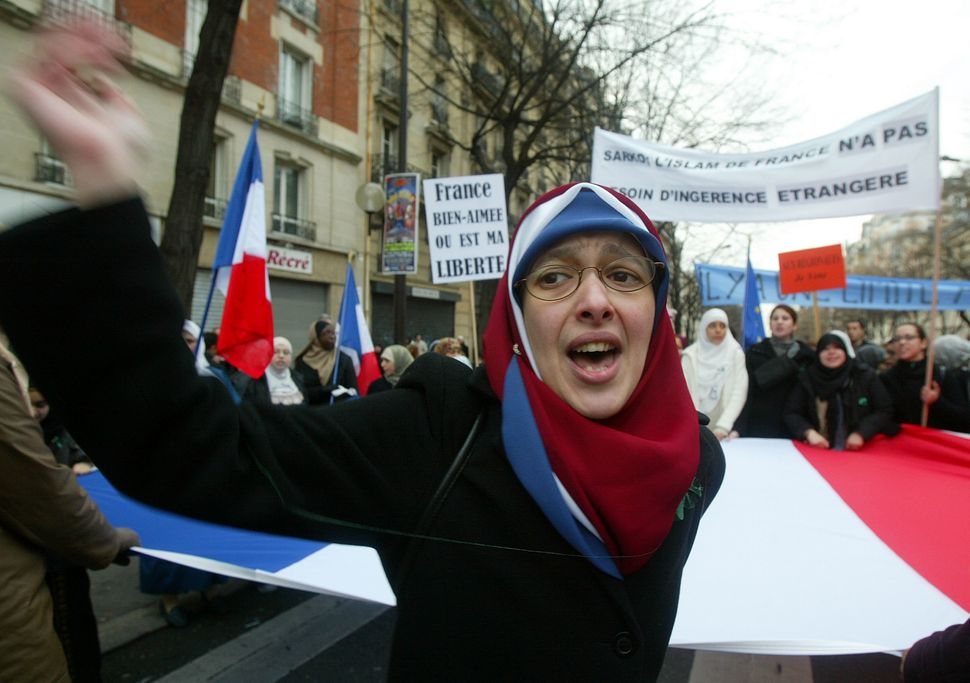 A Muslim woman demonstrates in the street against the French proposal to bar Muslim women from wearing headscarves in state s