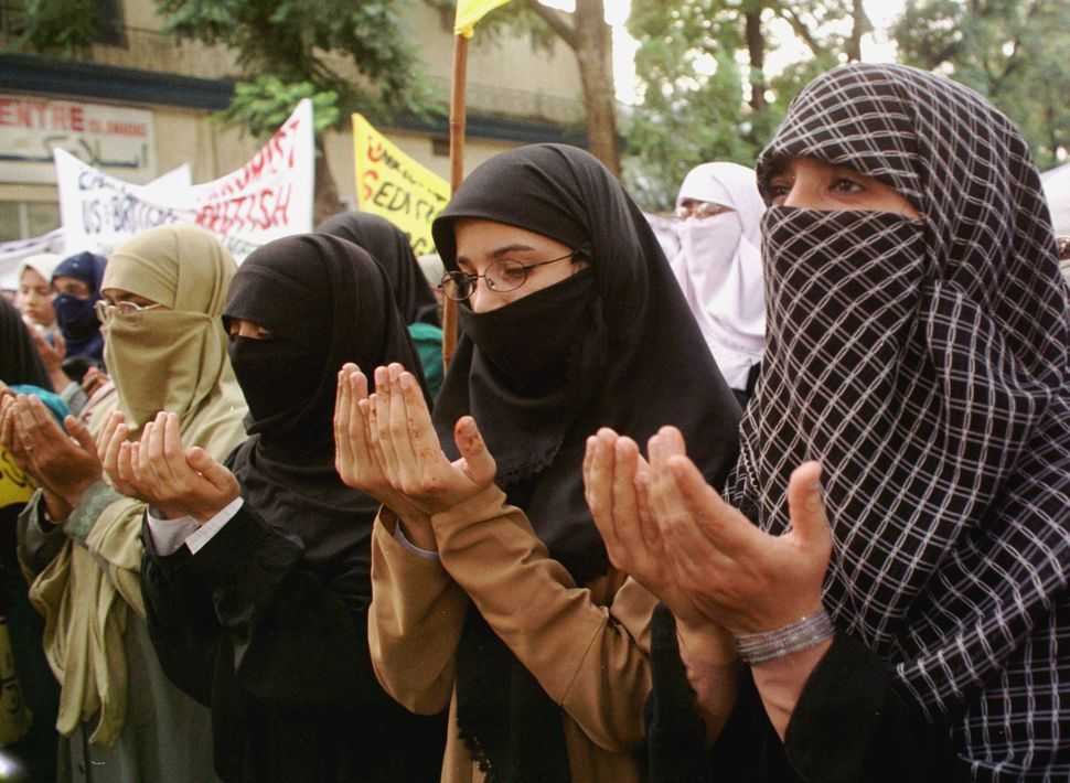 Pakistani women raise their hands in a prayer at a rally Oct. 6, 2001, in Islamabad, Pakistan. They condemned the terrorist a