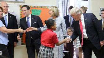 President Donald Trump greets fourth grader Janayah Chatelier as U.S. Secretary of Education Betsy DeVos greets St. Andrew Catholic School fourth grade teacher Jane Jones on March 3, 2017, in Orlando, Fla. Looking on is Florida governor Rick Scott, second from left, Florida senator Marco Rubio, third from left, and John Kirtley, far right, a tax-credit scholarship proponent. (Joe Burbank/Orlando Sentinel/TNS via Getty Images)