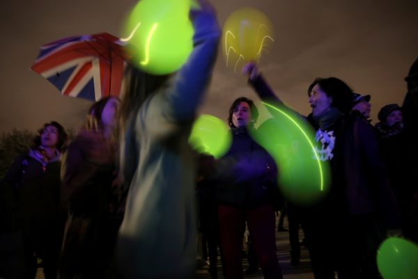 People play with lit balloons after the lights were switched off for Earth Hour at the Royal Palace in Madrid, Spain, March 2