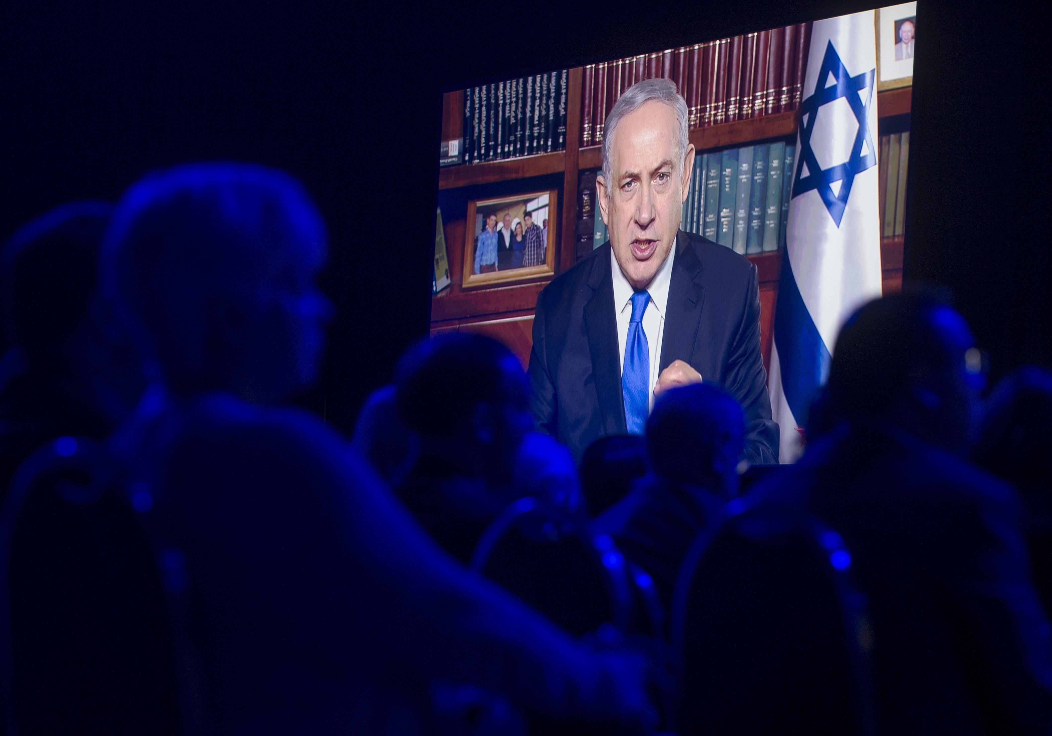 Israeli Prime Minister Benjamin Netanyahu speaks via a satellite television feed during the American Israel Public Affairs Co