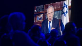 Israeli Prime Minister Benjamin Netanyahu speaks via a satellite television feed during the American Israel Public Affairs Committee (AIPAC) 2016 Policy Conference at the Washington Convention Center in Washington, DC, March 22, 2016. / AFP / SAUL LOEB        (Photo credit should read SAUL LOEB/AFP/Getty Images)