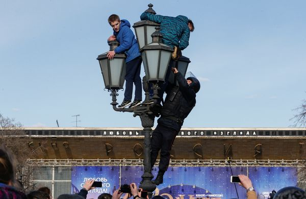 A law enforcement officer climbs a lamp pole to detain opposition supporters in Moscow.