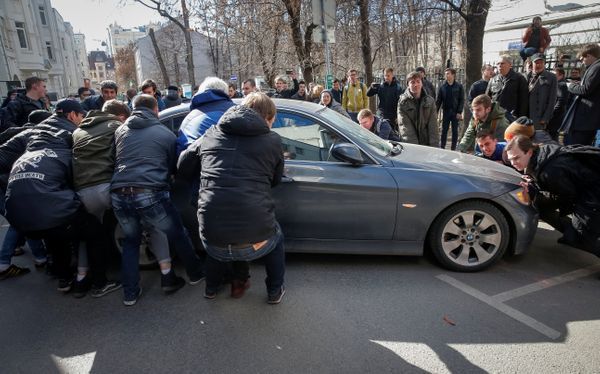 Opposition supporters move a car to block a van transporting detained anti-corruption campaigner and opposition figure Alexei