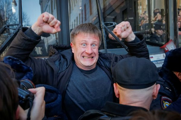 An opposition supporter blocks a police van transporting Navalny during a rally in Moscow.
