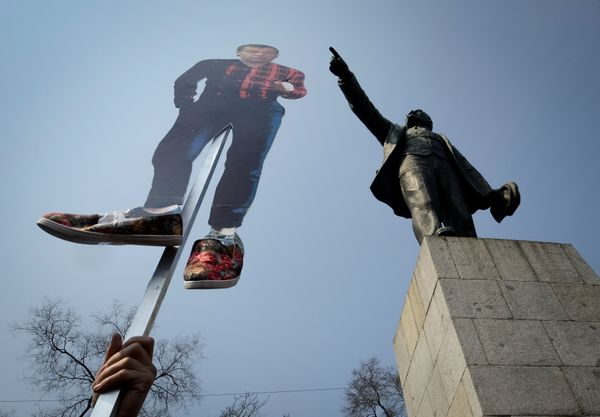 A opposition supporter holds a cutout figure depicting Prime Minister Dmitry Medvedev in Vladivostok.