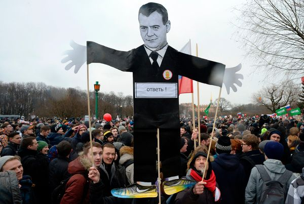 Protesters carry a cutout figure depicting Prime Minister Dmitry Medvedev in central Saint Petersburg.