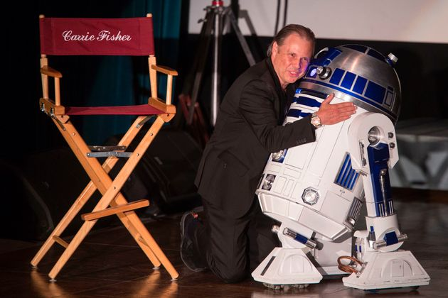 Todd Fisher hugs an R2-D2 robot near an empty chair for his late sister, actress Carrie Fisher, during...